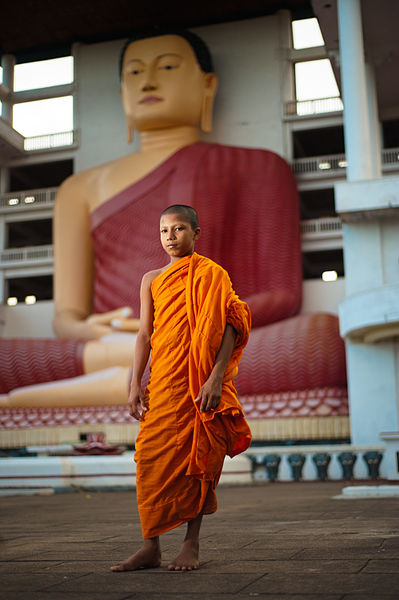 A_young_monk_against_the_background_of_Big_Buddha_statue_in_Weherahena_Temple._Matara,_Southern_Province,_Sri_Lanka